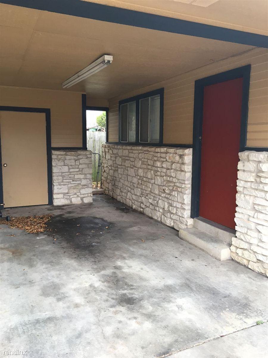 Carport space with laundry hook ups behind the door.