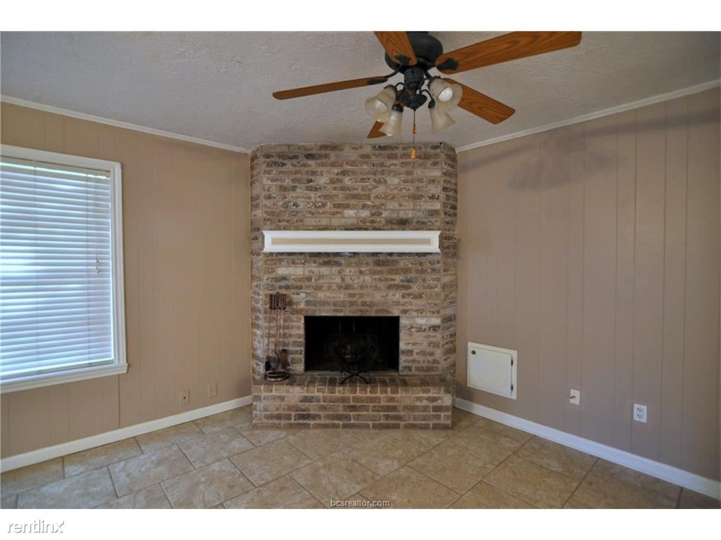 Living room floor is all tiled with a wood burning fireplace