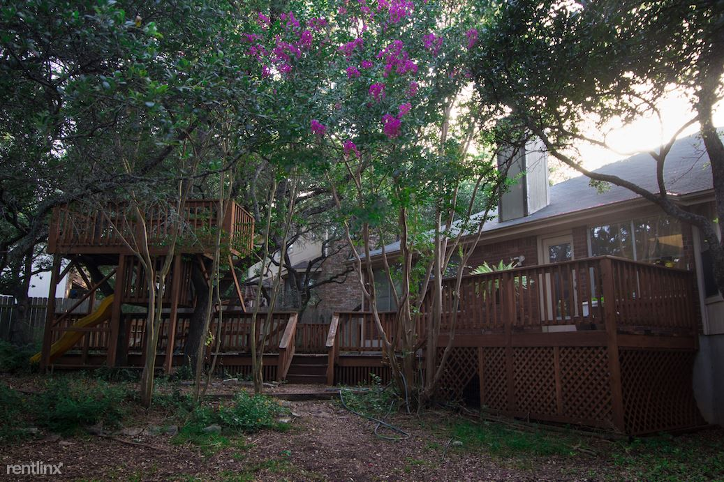 Back yard with large deck and built-in treehouse/playscape with slide and lots of shady oaks
