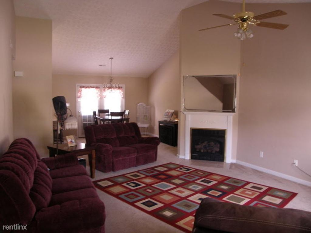 View of fireplace in living room with dining area and door to deck behind