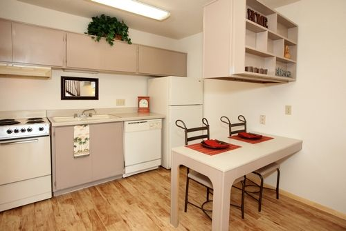 Kitchen with built-in breakfast bar and decorative shelves.